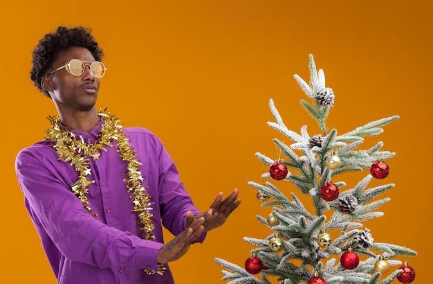 Unzufriedener junger afroamerikanischer mann, der eine brille mit lametta-girlande um den hals trägt, die in der nähe des geschmückten weihnachtsbaums steht und ihn bei der ablehnungsgeste lokalisiert auf orange wand betrachtet