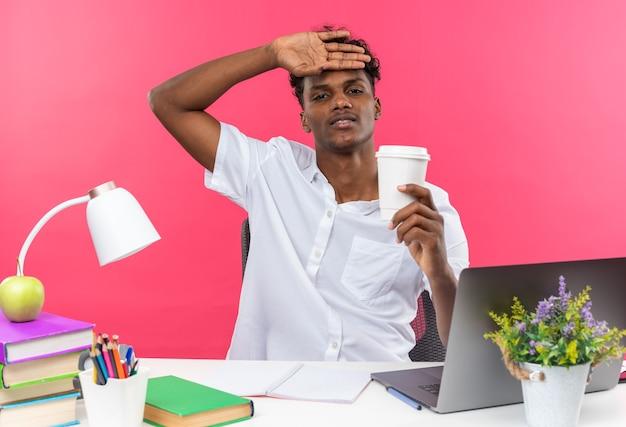 Unzufriedener junger afroamerikanischer student, der am schreibtisch mit schulwerkzeugen sitzt, die hand auf seine stirn legt und pappbecher hält