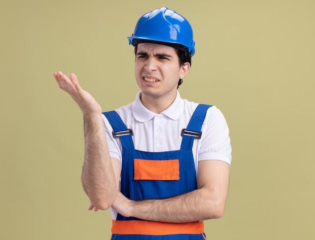 Unzufriedener junger baumeister in bauuniform und schutzhelm, der beiseite schaut, um hand in unmut und empörung zu erheben, die über grüner wand stehen
