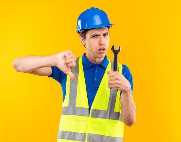 Unzufriedener junger baumeister in uniform, der einen gabelschlüssel hält, der daumen nach unten zeigt, isoliert auf gelber wand