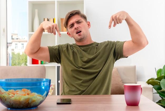 Unzufriedener junger blonder gutaussehender mann sitzt am tisch mit schüssel schüssel chips telefon und tasse, die unten mit zwei händen im wohnzimmer zeigen