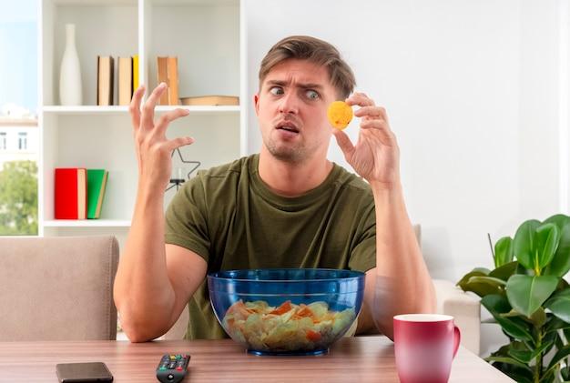 Unzufriedener junger blonder gutaussehender mann sitzt am tisch mit telefonschüssel chips und tasse hebt hand und betrachtet chips im wohnzimmer