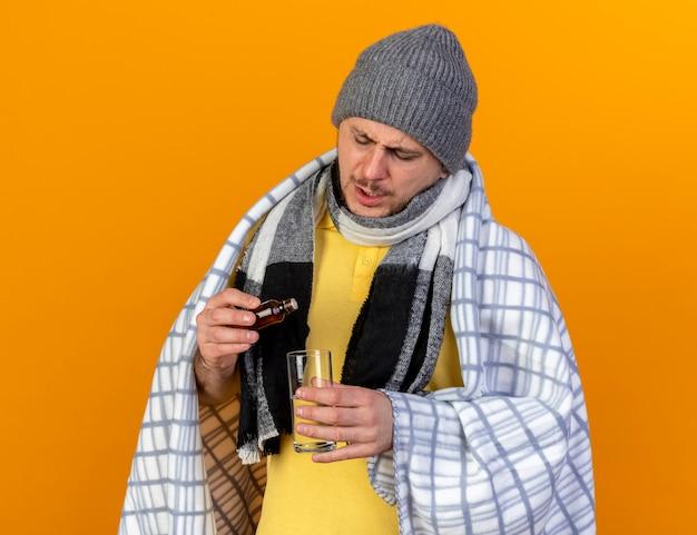 Unzufriedener junger blonder kranker slawischer mann, der wintermütze und schal in plaid gewickelt hält, hält glas wasser und medizin in glasflasche lokalisiert auf orange wand mit kopienraum