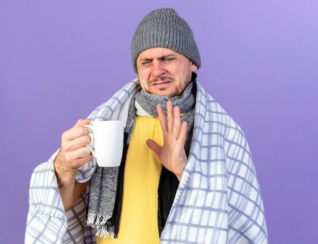 Unzufriedener junger blonder kranker slawischer mann, der wintermütze und schal trägt