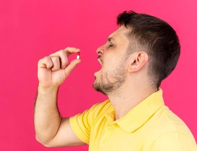 Unzufriedener junger blonder kranker slawischer mann steht seitwärts und gibt vor, medizinische kapsel auf rosa zu nehmen