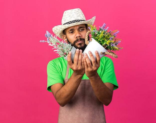 Unzufriedener junger gärtner afroamerikanischer mann mit gartenhut, der blumen im blumentopf hält und betrachtet