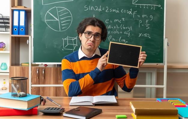 Unzufriedener junger geometrielehrer mit brille, der am schreibtisch mit schulmaterial im klassenzimmer sitzt und eine mini-tafel mit blick auf die vorderseite zeigt