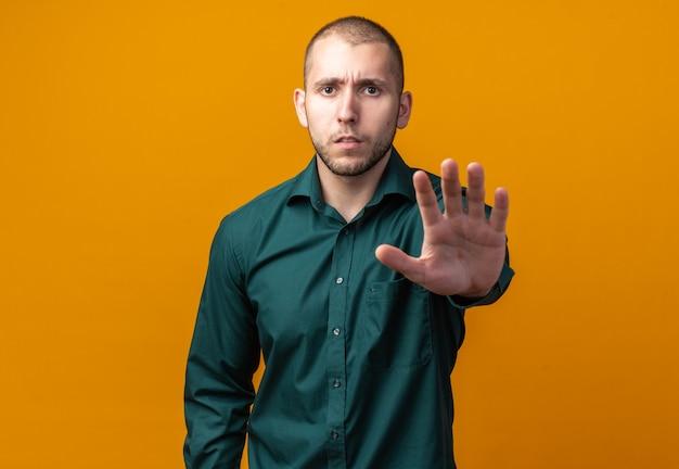 Unzufriedener junger gutaussehender kerl mit grünem hemd, der mit der hand eine stoppgeste macht