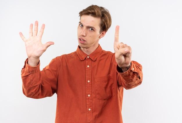 Unzufriedener junger gutaussehender kerl mit rotem hemd, das verschiedene nummern isoliert auf weißer wand zeigt