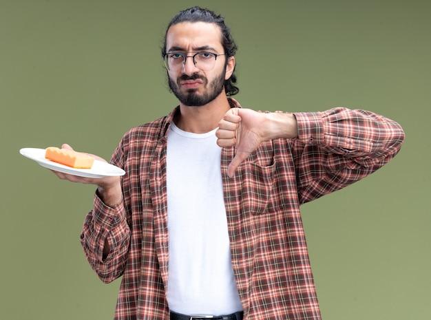 Unzufriedener junger gutaussehender putzmann, der t-shirt hält, das schwamm auf platte hält, zeigt daumen unten lokalisiert auf olivgrüner wand