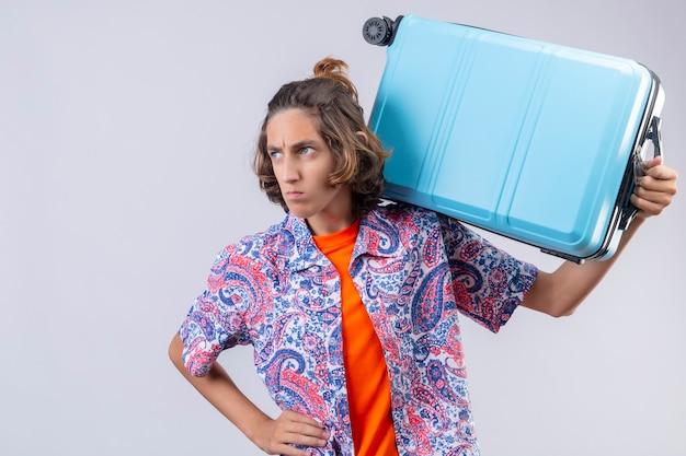Unzufriedener junger gutaussehender reisender, der koffer auf schulter hält und mit stirnrunzelndem gesicht beiseite schaut