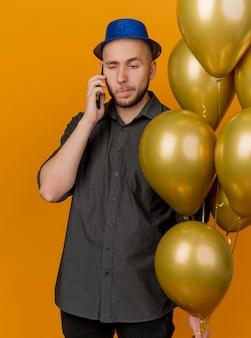 Unzufriedener junger gutaussehender slawischer party-typ, der partyhut hält, der ballone hält, die am telefon sprechen, lokalisiert auf orange hintergrund