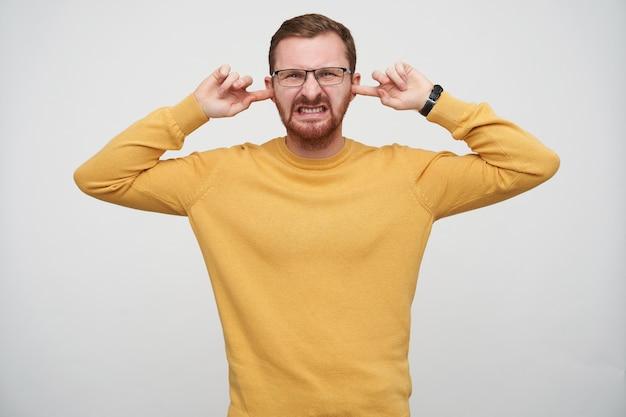 Unzufriedener junger hübscher bärtiger brünetter mann in brille mit kurzem haarschnitt, geschlossenen augen und stirnrunzelndem gesicht unter vermeidung lauter geräusche, isoliert