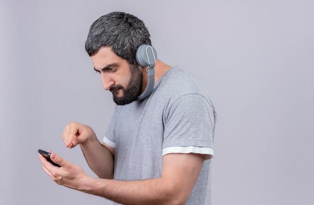 Unzufriedener junger hübscher kaukasischer mann, der kopfhörer trägt und sein handy lokalisiert auf weißem hintergrund mit kopienraum betrachtet