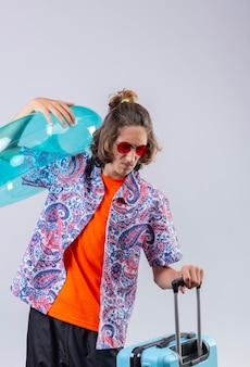 Unzufriedener junger hübscher kerl, der rote sonnenbrille hält, die aufblasbaren ring hält, genervt mit stehendem reisekoffer