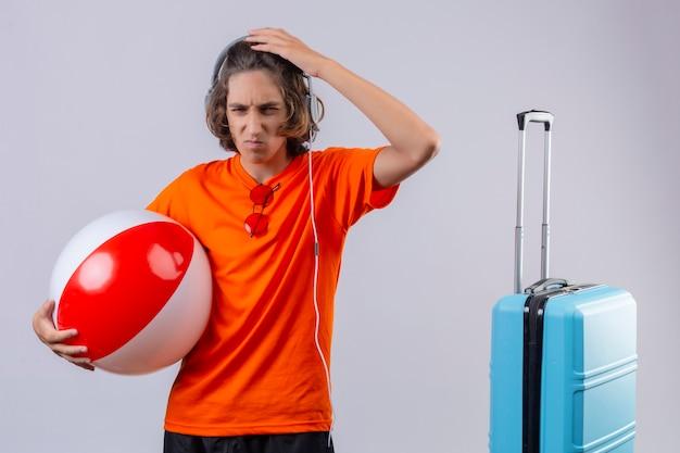 Unzufriedener junger hübscher kerl im orangefarbenen t-shirt mit kopfhörern, die aufblasbaren ball berührenden kopf halten, der eine kamera mit stirnrunzelndem gesicht in der nähe des koffers steht