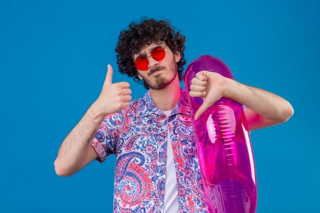 Unzufriedener junger hübscher lockiger mann, der sonnenbrille hält, die schwimmring zeigt, der daumen oben und unten auf isolierter blauer wand zeigt