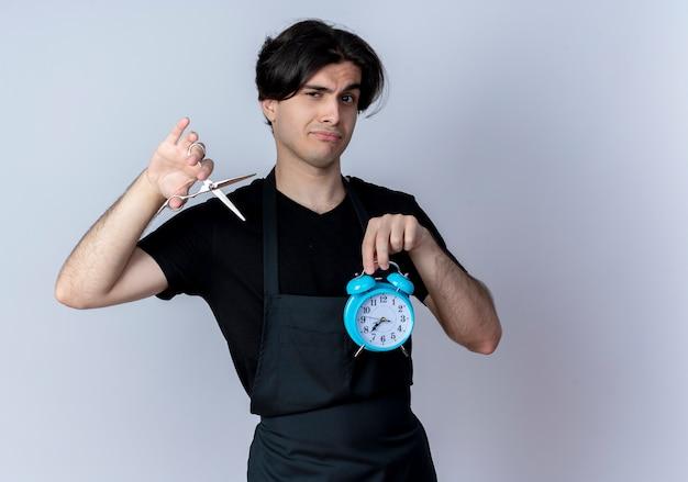 Unzufriedener junger hübscher männlicher friseur in uniform, der wecker mit schere lokalisiert auf weißer wand hält