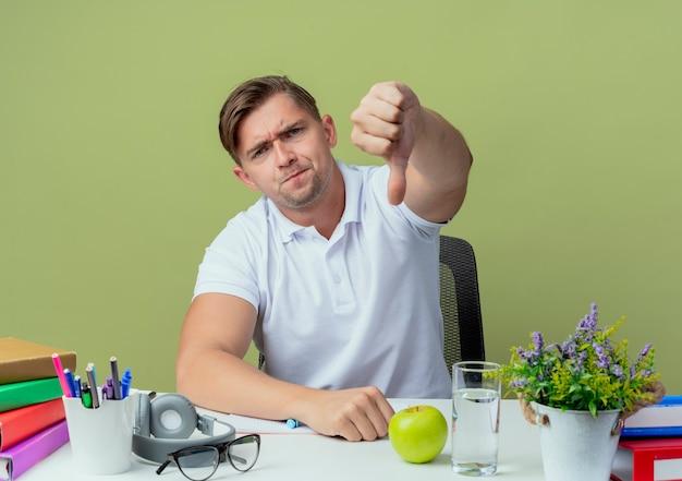 Unzufriedener junger hübscher männlicher student, der am schreibtisch sitzt