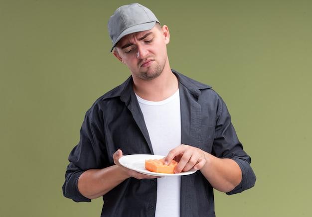 Unzufriedener junger hübscher putzmann, der t-shirt und kappe hält platte mit schwamm lokalisiert auf olivgrüner wand trägt