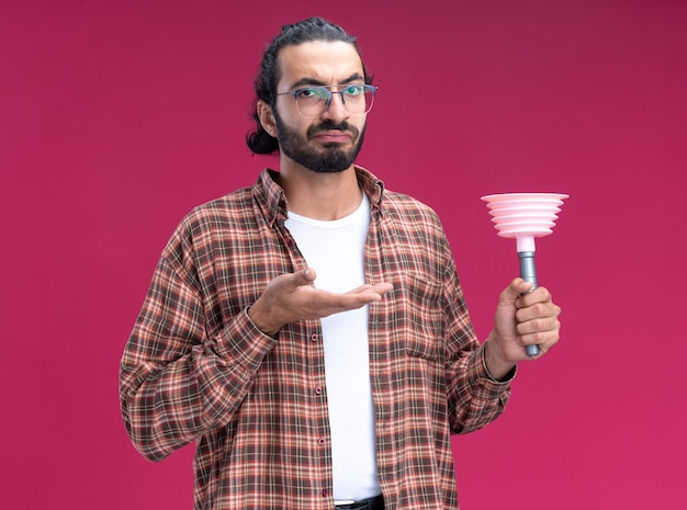Unzufriedener junger hübscher reinigungsmann, der t-shirt hält und punkte auf kolben lokalisiert auf rosa wand trägt
