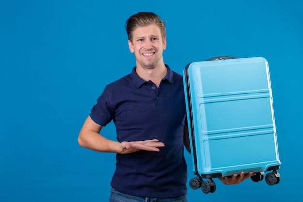 Unzufriedener junger hübscher reisender mann, der koffer hält, der mit arm seiner hand mit verwirrendem ausdruck auf gesicht präsentiert, das über blauem raum steht