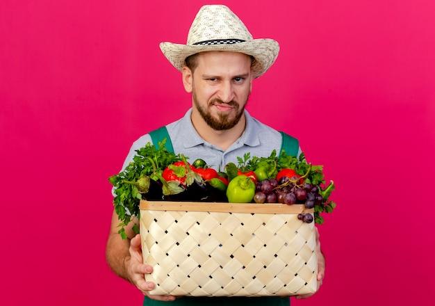 Unzufriedener junger hübscher slawischer gärtner in uniform und hut, der korb des gemüses lokalisiert auf purpurroter wand mit kopienraum hält
