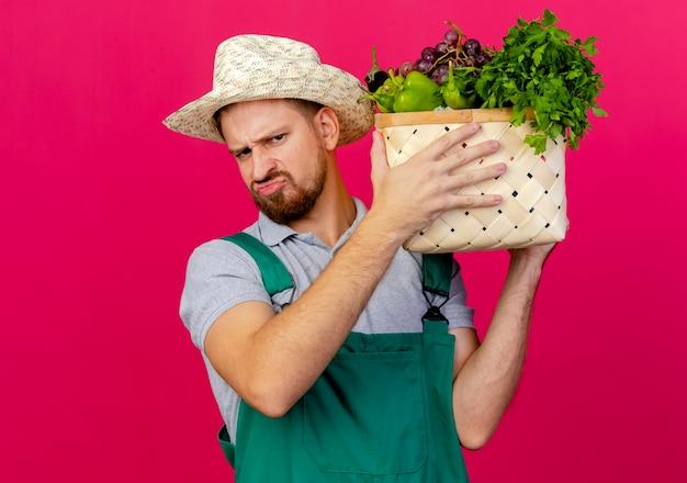 Unzufriedener junger hübscher slawischer gärtner in uniform und hut, die korb des gemüses nahe kopf suchen