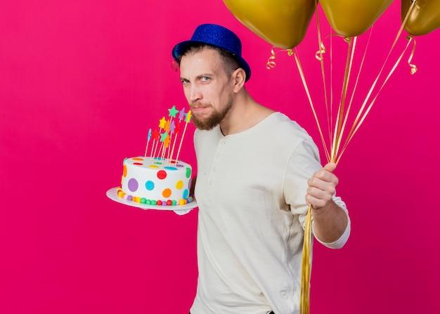 Unzufriedener junger hübscher slawischer partei-kerl, der parteihut trägt, der in der profilansicht hält, die luftballons und geburtstagstorte mit sternen hält, die kamera betrachten, die auf purpurrotem hintergrund mit kopienraum isoliert wird