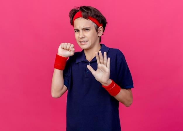 Unzufriedener junger hübscher sportlicher junge, der stirnband und armbänder mit zahnspangen trägt, die faust ballen, die front betrachtet und keine geste tut, die auf rosa wand mit kopienraum isoliert wird