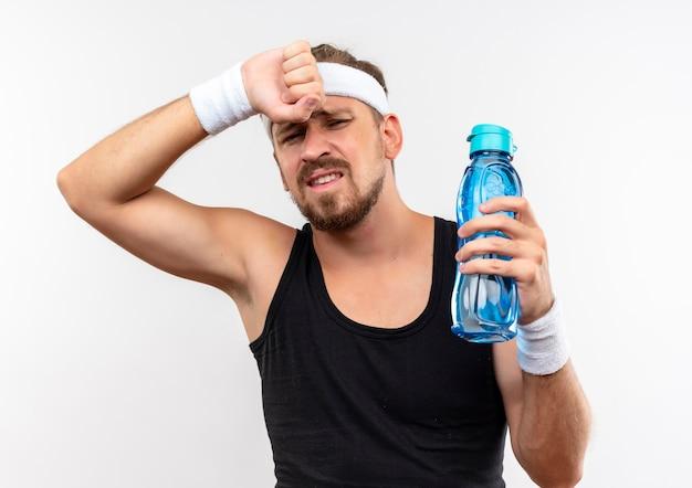 Unzufriedener junger hübscher sportlicher mann, der stirnband und armbänder hält, die wasserflasche mit hand auf kopf halten, lokalisiert auf weißem raum