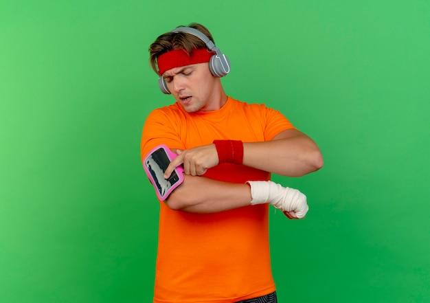 Unzufriedener junger hübscher sportlicher mann, der stirnband und armbänder trägt, die finger auf telefonarmband mit verletztem handgelenk setzen, das mit verband umwickelt wird, der auf grünem hintergrund mit kopienraum isoliert wird
