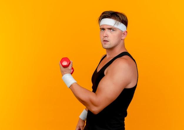 Unzufriedener junger hübscher sportlicher mann, der stirnband und armbänder trägt, die in der profilansicht halten hantel lokalisiert auf orangefarbenem hintergrund mit kopienraum stehen