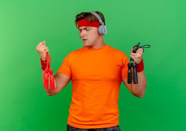 Unzufriedener junger hübscher sportlicher mann, der stirnband und armbänder und kopfhörer trägt, die springseile halten und einen von ihnen lokalisiert auf grünem hintergrund betrachten
