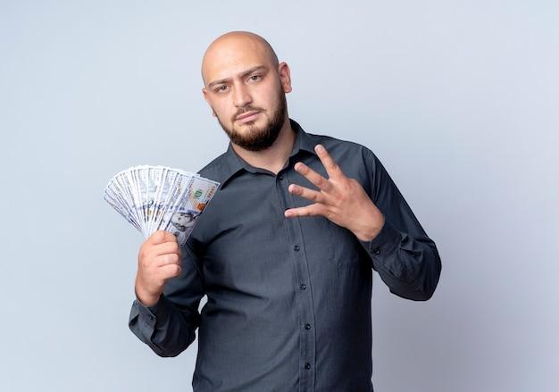 Unzufriedener junger kahlköpfiger callcenter-mann, der geld hält und vier lokalisiert auf weißem hintergrund zeigt