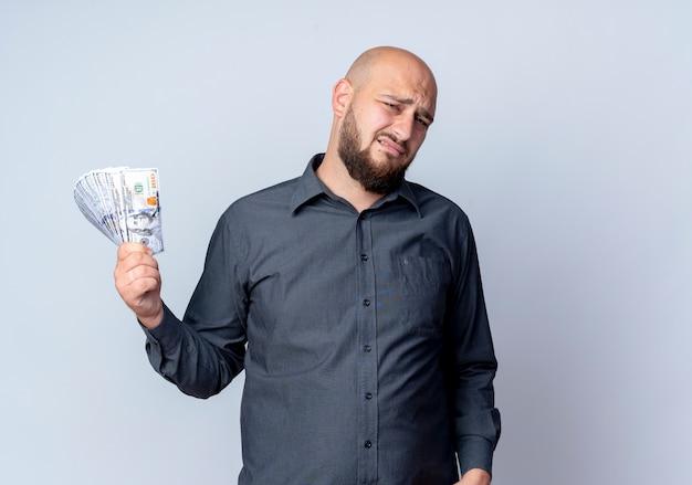 Unzufriedener junger kahlköpfiger callcenter-mann, der geld lokalisiert auf weißem hintergrund mit kopienraum hält