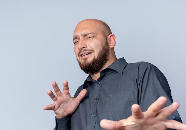 Unzufriedener junger kahlköpfiger callcenter-mann, der hand ausstreckt, die nicht auf kamera lokalisiert auf weißem hintergrund gestikuliert