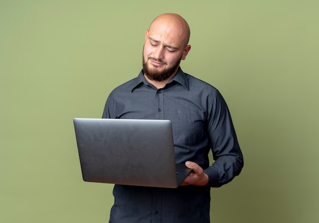 Unzufriedener junger kahlköpfiger callcenter-mann, der laptop lokalisiert auf olivgrünem hintergrund mit kopienraum hält und betrachtet