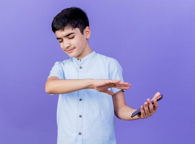 Unzufriedener junger kaukasischer junge, der handy hält, das keine geste mit hand mit geschlossenen augen tut, lokalisiert auf lila hintergrund mit kopienraum