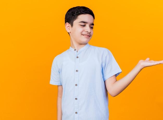 Unzufriedener junger kaukasischer junge, der leere hand zeigt, die es lokalisiert auf orange hintergrund mit kopienraum betrachtet