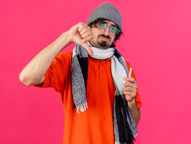 Unzufriedener junger kaukasischer kranker mann, der brille wintermütze und schal hält, die thermometer betrachten kamera betrachten daumen unten isoliert auf purpurrotem hintergrund mit kopienraum