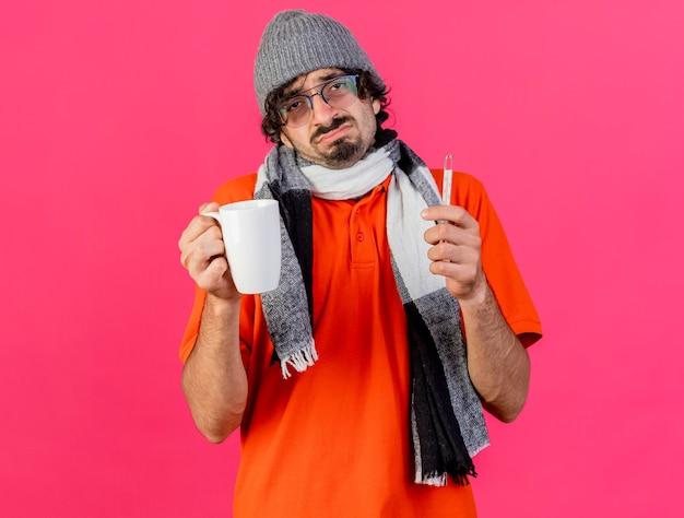 Unzufriedener junger kaukasischer kranker mann, der brille wintermütze und schal hält tasse und thermometer trägt kamera betrachtet auf purpurrotem hintergrund mit kopienraum