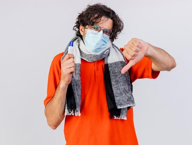 Unzufriedener junger kaukasischer kranker mann, der brillenschal und maske hält, die thermometer betrachten kamera betrachten daumen unten isoliert auf weißem hintergrund
