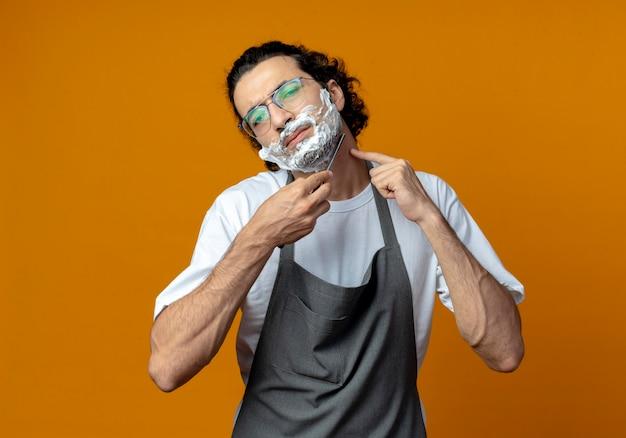 Unzufriedener junger kaukasischer männlicher barbier mit brille in uniform, der seinen bart mit einem rasiermesser rasiert, mit rasierschaum auf sein gesicht setzt und den finger auf den hals legt
