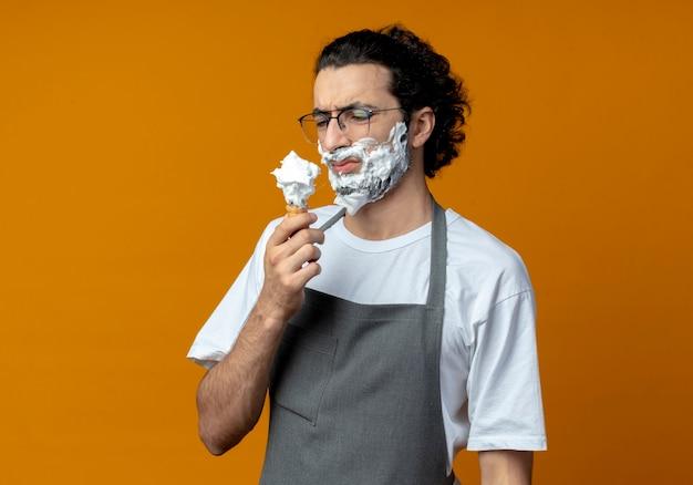 Unzufriedener junger kaukasischer männlicher barbier mit brille und welligem haarband in uniform, der den rasierpinsel mit rasierschaum auf seinem bart hält und betrachtet