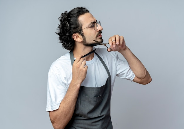 Unzufriedener junger kaukasischer männlicher barbier mit brille und welligem haarband in uniform, der seinen bart schneidet und kämmt, der auf die seite schaut