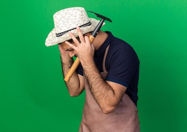 Unzufriedener junger kaukasischer männlicher gärtner, der gartenhut trägt, setzt hände auf kopf, der rechen lokalisiert auf grüner wand mit kopienraum hält