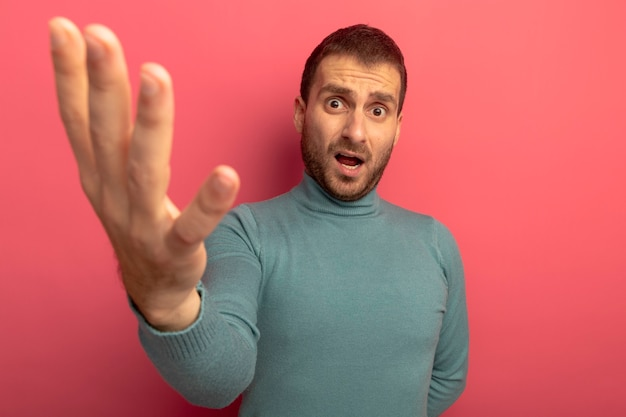 Unzufriedener junger kaukasischer mann, der kamera betrachtet, die hand in richtung kamera streckt, die auf purpurrotem hintergrund mit kopienraum lokalisiert wird