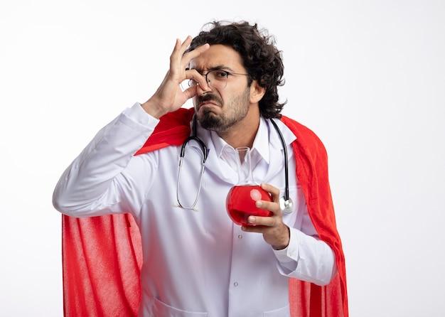 Unzufriedener junger kaukasischer mann in der optischen brille, die arztuniform mit rotem umhang und mit stethoskop um hals trägt, schließt nase und hält rote chemische flüssigkeit im glaskolben auf weißer wand
