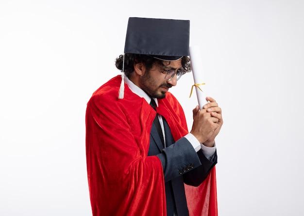 Unzufriedener junger kaukasischer superheldenmann in optischer brille, der anzug mit rotem mantel und abschlusskappe trägt, hält und betrachtet diplom
